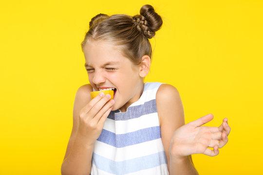 Young girl eating lemon on yellow background