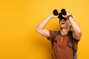 handsome pensive traveler looking through binoculars on yellow