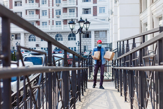 food delivery man with bags in a protective mask on his face