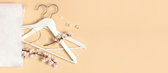 Creative spring sale concept. White wooden hangers with spring flowers white paper bag on beige background top view flat lay. Fashion spring discounts shopping sale store promo design minimalism style