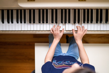 directly above view of young boy playing the piano at home Wall mural
