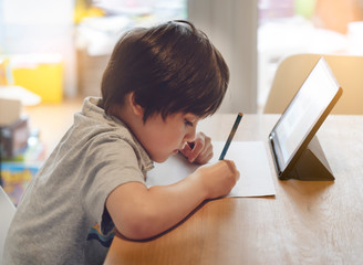 Portrait of preschool kid using tablet for his homework,Soft focus of Child doing homework by using...