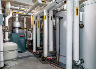 Boiler room of residential, strata or multilevel building. 3 hot water boiler visible. Many insulated pipes with yellow arrows to direction of water flow.