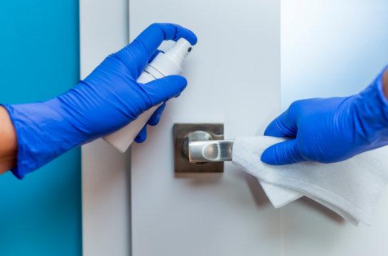 Decontaminating the surface of the door handle. Coronavirus prevention, hygiene to stop spreading coronavirus.