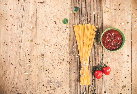 Uncooked spaghetti on wooden table . Topview of dried noodle