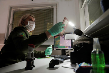 A Belarusian border guard wearing gloves to protect herself from the coronavirus disease (COVID-19) checks a passport, at the border check point between Belarus and Lithuania