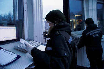 A Belarusian border guard wearing a face mask and gloves to protect herself from the coronavirus disease (COVID-19) checks a passport, at the border check point between Belarus and Lithuania