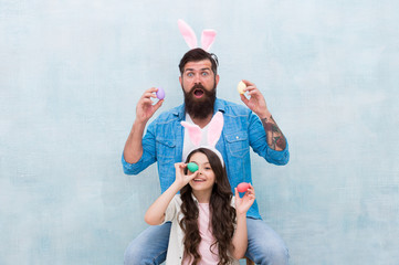easter egg hunt. happy family wear bunny ears. fun and happiness. father and daughter hold easter eggs. spring holiday party. small kid girl and dad in rabbit costume. painted eggs