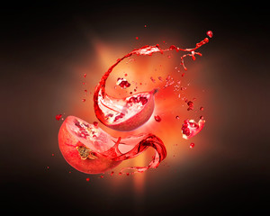 Juice splashes out from chopped pomegranate with flash of light in the dark
