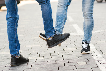 Low section of men greeting each other with feet