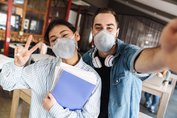 Photo of students in medical masks taking selfie and showing peace sign