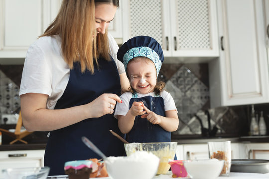 Cute little girl and her beautiful mom in matching aprons and caps play and laugh while kneading dough in the kitchen.