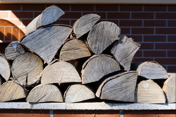 Tuinposter Brandhout textuur A pile of firewood lying on a wall lit by the sun