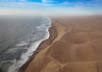 Foto auf Acrylglas Küste Aerial picture of the landscape of the Namib Desert and the Atlantic Ocean on the Skeleton Coast in western Namibia