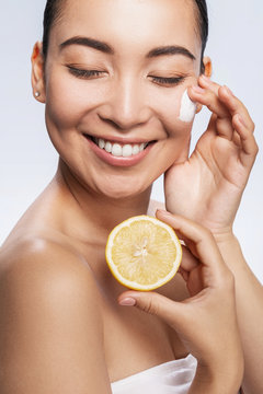 Smiling pretty lady posing with lotion and lemon