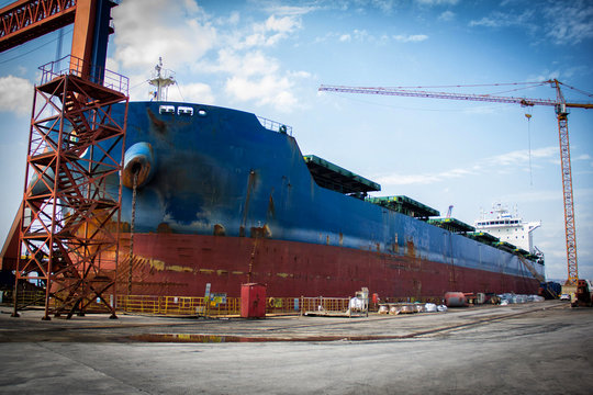 A large tanker kargo ship is being renovated and painted in shipyard dry dock.