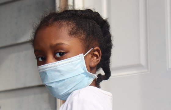Girl wearing blue surgical mask outside house