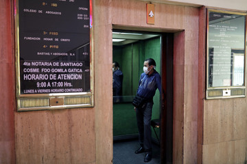 An elevator operator wears a preventive mask while waiting for people, in Santiago