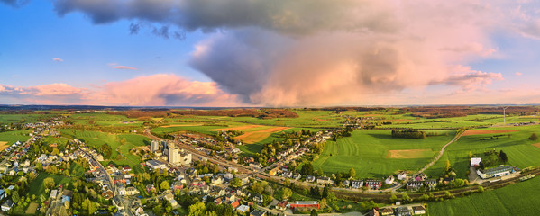 Foto auf Leinwand Rosa hell Storm cloud during sunset over town