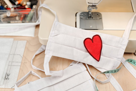 Homemade facemask against virus infection in detail with sewing machine and heart emblem