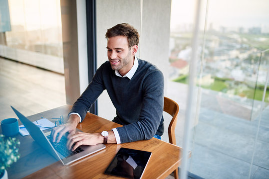 Smiling young businessman working from home on a laptop