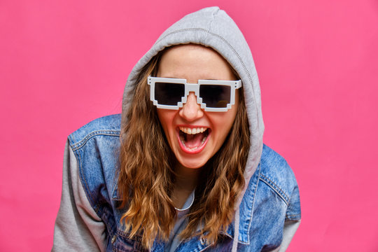 Stylish Caucasian girl in a blue jeans and 8-bit glasses and laughs at the camera on a pink background.