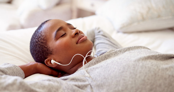 Smiling young woman listening to music on her bed
