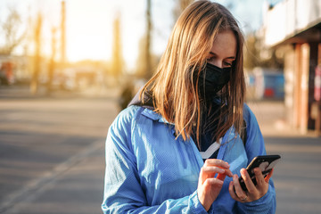 Coronavirus in Europe. the girl is standing by the road in a protective medical mask and talking on a cell phone.