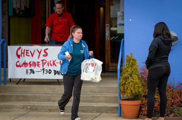 Emily Ashcraft picks up food from Chevy's Fresh Mex restaurant's curb side service because the restaurant is closed to prevent the spread of coronavirus disease (COVID-19) in Annapolis