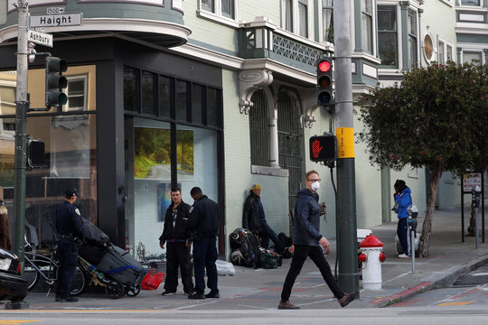 A man walks with a face mask on as the San Francisco police question a man, during day two of the citywide shelter in place order amid the outbreak of coronavirus disease (COVID-19), in the Haight-Ashbury section of San Francisco, California