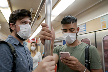 Students and travelers using public transport for commuting. Covid-19 and CoronaVirus concept. People wearing masks on the train. Fototapete