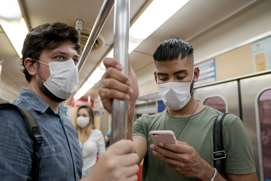 Students and travelers using public transport for commuting. Covid-19 and CoronaVirus concept. People wearing masks on the train.