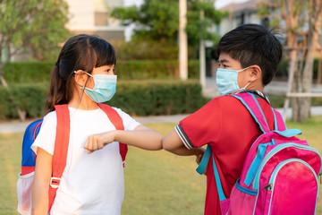 Elbow bump is new novel greeting to avoid the spread of coronavirus. Two Asian children preschool...
