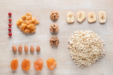 Dry oat grains with fruits and nuts on wooden background