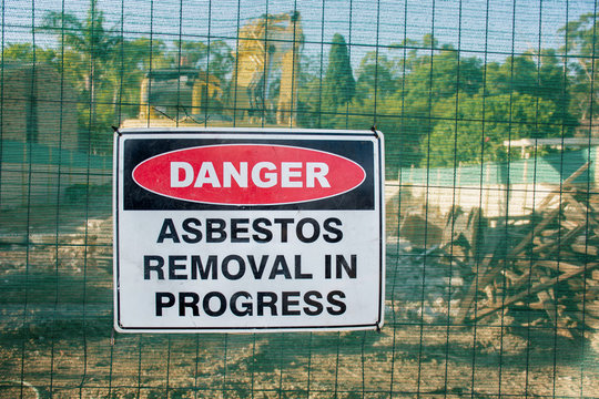 A warning sign Danger Asbestos on a fence at construction site where old house is demolishing