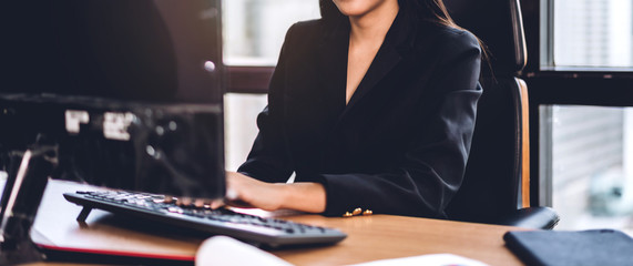 Confident asian businesswoman relaxing looking at technology of desktop computer while sitting on office desk.Young creative coworkers business people working and typing on keyboard at office Wall mural