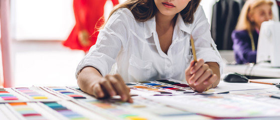 Portrait of young beautiful pretty woman fashion designer stylish sitting and working with color samples.Attractive young girl working with mannequins standing and colorful fabrics at fashion studio Wall mural