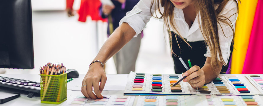 Portrait of young beautiful pretty woman fashion designer stylish stand and working with color textile samples.Attractive  senior woman working with mannequins and colorful fabrics at fashion studio
