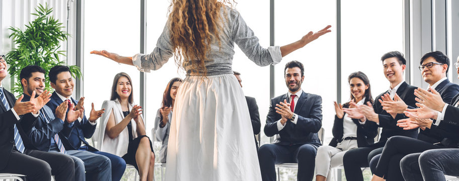 Businesswoman coach speaker presentation and discussing meeting strategy sharing ideas thoughts.Creative work group of casual business people clapping hands in modern office.Success concept
