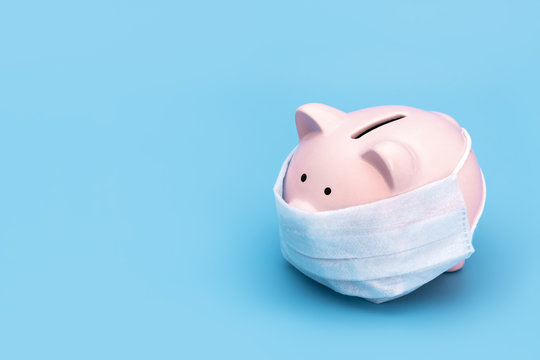 Pink piggy Bank stands on a blue medical background in a medical mask, on the right there is an empty space for the text. Chinese Coronavirus, 2019-nCoV