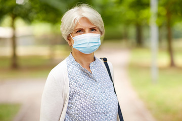 health, safety and pandemic concept - portrait of senior woman wearing protective medical mask for...
