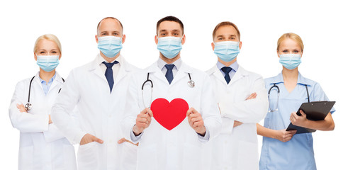 medicine, cardiology and healthcare concept - group of doctors wearing protective medical masks...