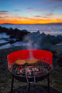 Grilling burgers on a small metal portable charcoal grill on the shores of Lac Leman in Switzerland during early winter evening with sun setting down