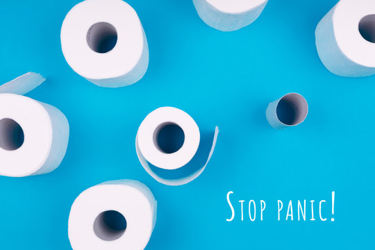 Toilet paper rolls on the bright blue background with Stop panic wording. Coronavirus pandemic panic shopping concept. Bright monochrome drop