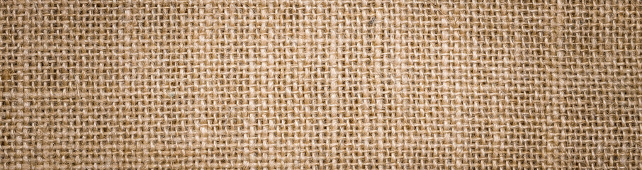Obraz Rough hessian background with flecks of varying colors of beige and brown. with copy space. office desk concept, Hessian sackcloth burlap woven texture background. - fototapety do salonu