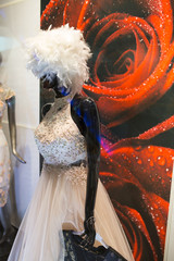 Female mannequin in a showcase with a wig of feathers on her head and a white dress.