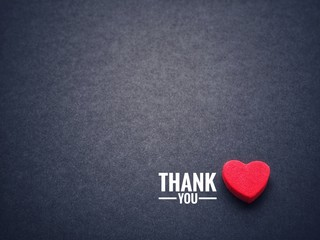Fototapeta The words thank you and the red heart on the black paper background. obraz
