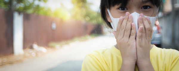 Young Asian girl wearing mask for protect covid 19, Thai kid wear dust mask. Protect pm 2.5 and stop  corona virus concept