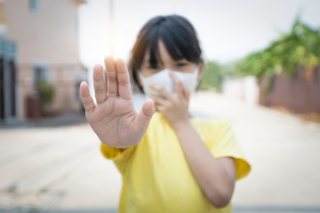 Young Asian girl wearing mask for protect covid 19, Thai kid wear dust mask. for protect pm2.5 and show stop hands gesture for stop corona virus outbreak.