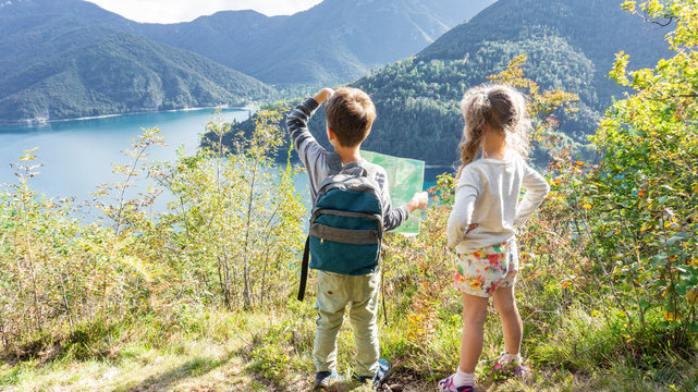 Two scout children stand on a tourist route along a camping road on the shore of a mountain lake Ledro in the Alps. Kids hiking in the forest in Alps mountains